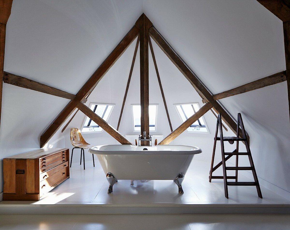 Freistehende Badewanne im Erker unter dem Dach mit Sichtbalken